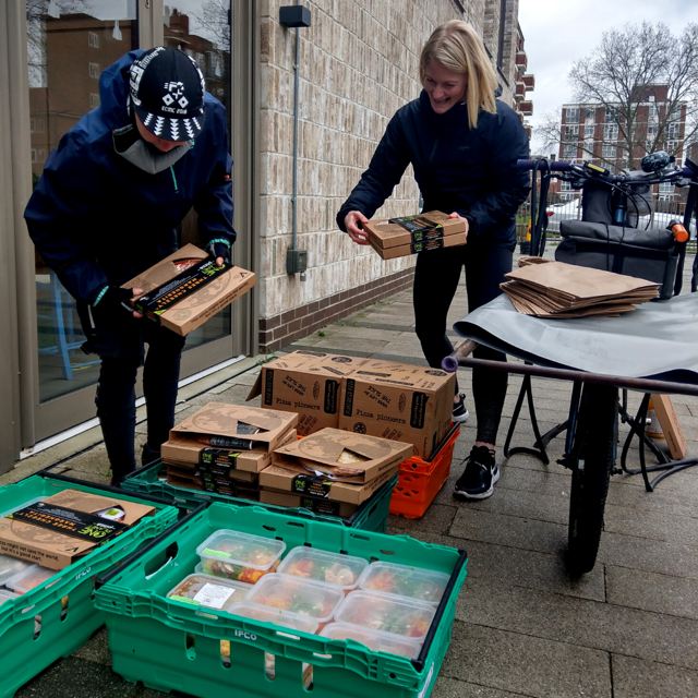 Members of the Made in Hackney and One Planet Pizza teams working together on pizza deliveries.